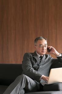 ソファーに座りノートパソコンを操作するビジネスマンの写真素材 [FYI04546215]