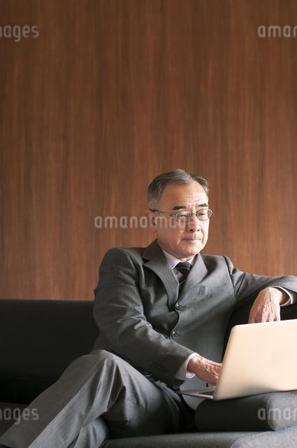 ソファーに座りノートパソコンを操作するビジネスマンの写真素材 [FYI04546216]