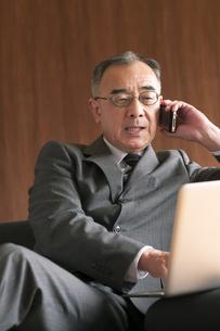 ソファーに座りノートパソコンを操作するビジネスマンの写真素材 [FYI04546223]