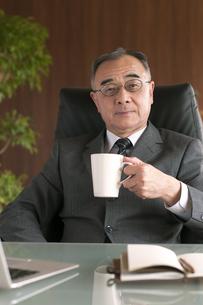 コーヒーカップを持つビジネスマンの写真素材 [FYI04546254]