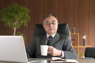 コーヒーカップを持つビジネスマンの写真素材 [FYI04546256]