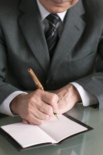 手帳にメモをするビジネスマンの手元の写真素材 [FYI04546261]