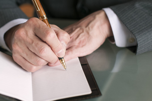手帳にメモをするビジネスマンの手元の写真素材 [FYI04546263]