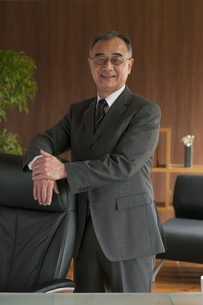 椅子に手をかけるビジネスマンの写真素材 [FYI04546265]