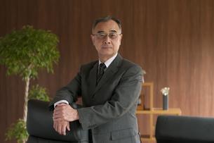 椅子に手をかけるビジネスマンの写真素材 [FYI04546268]