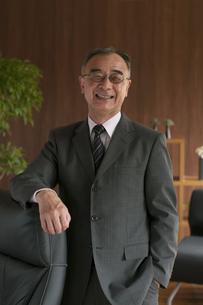椅子に手をかけるビジネスマンの写真素材 [FYI04546271]