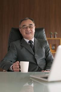 椅子に座りコーヒーカップを持つビジネスマンの写真素材 [FYI04546278]