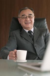 椅子に座りコーヒーカップを持つビジネスマンの写真素材 [FYI04546283]