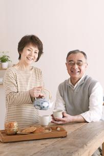 お茶をいれるシニア夫婦の写真素材 [FYI04546376]
