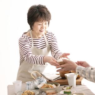 ご飯を手渡すシニア女性の写真素材 [FYI04546421]