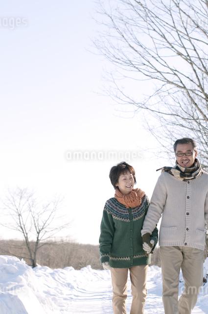 雪道を歩くシニア夫婦の写真素材 [FYI04546476]