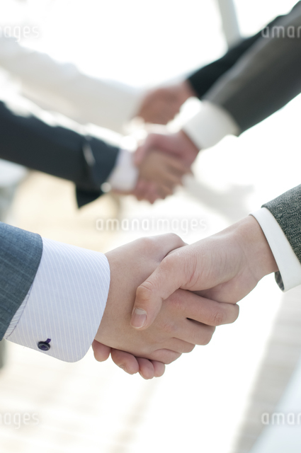 握手をするビジネスマンとビジネスウーマンの手元の写真素材 [FYI04546603]