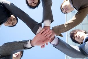円陣を組むビジネスマンとビジネスウーマンの写真素材 [FYI04546624]