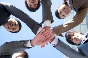 円陣を組むビジネスマンとビジネスウーマンの写真素材 [FYI04546626]