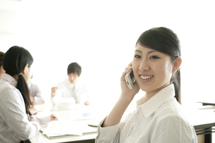 スマートフォンで電話をするビジネスウーマンの写真素材 [FYI04546737]