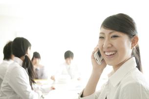 スマートフォンで電話をするビジネスウーマンの写真素材 [FYI04546741]