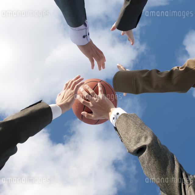 バスケットをするビジネスマンとビジネスウーマンの手元の写真素材 [FYI04546744]