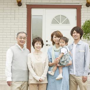 玄関前で微笑む3世代家族の写真素材 [FYI04546797]