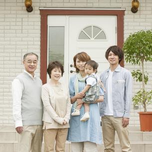 玄関前で微笑む3世代家族の写真素材 [FYI04546798]