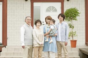 玄関前で微笑む3世代家族の写真素材 [FYI04546799]