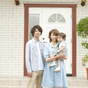 玄関前で微笑む家族の写真素材 [FYI04546800]