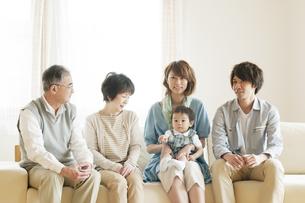 ソファに座り微笑む3世代家族の写真素材 [FYI04546802]