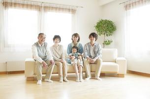 ソファに座り微笑む3世代家族の写真素材 [FYI04546807]