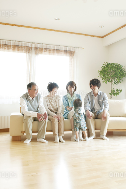 ソファに座り微笑む3世代家族の写真素材 [FYI04546810]