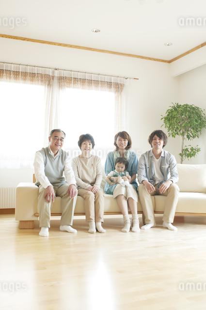 ソファに座り微笑む3世代家族の写真素材 [FYI04546812]