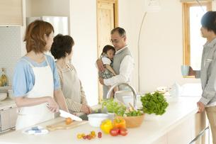 キッチンに集まる3世代家族の写真素材 [FYI04546823]