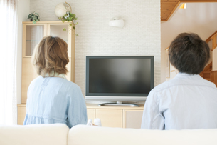 テレビを見る夫婦の後姿の写真素材 [FYI04546826]