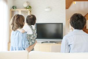 テレビを見る親子の後姿の写真素材 [FYI04546828]
