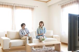 ソファに座りテレビを見る夫婦の写真素材 [FYI04546832]
