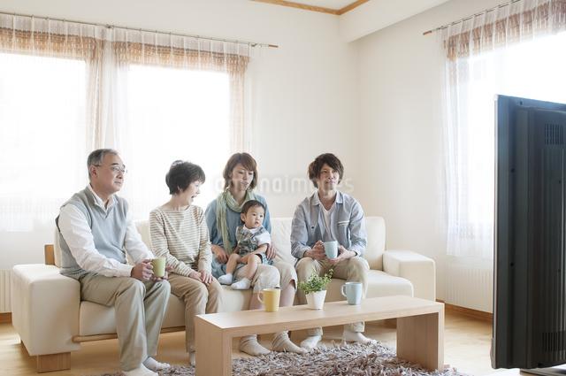 ソファに座りテレビを見る3世代家族の写真素材 [FYI04546834]