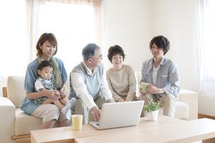 ノートパソコンを見る3世代家族の写真素材 [FYI04546848]