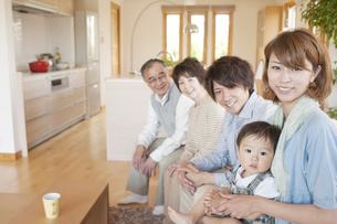 ソファに座り微笑む3世代家族の写真素材 [FYI04546850]