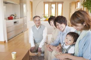ソファに座り微笑む3世代家族の写真素材 [FYI04546851]