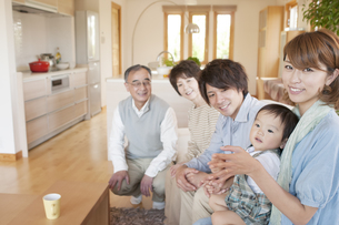 ソファに座り微笑む3世代家族の写真素材 [FYI04546857]