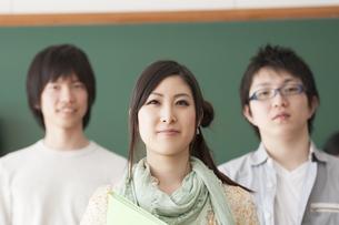 黒板の前で微笑む大学生の写真素材 [FYI04546918]