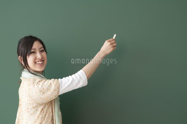 黒板に文字を書こうとする大学生の写真素材 [FYI04546927]