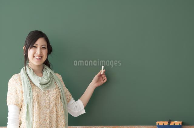 黒板の前で微笑む大学生の写真素材 [FYI04546931]