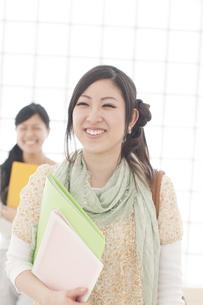 ファイルを持ち微笑む大学生の写真素材 [FYI04547039]