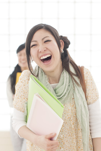 ファイルを持ち微笑む大学生の写真素材 [FYI04547040]
