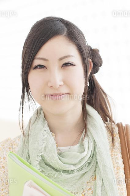 ファイルを持ち微笑む大学生の写真素材 [FYI04547062]