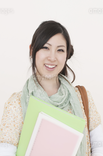 ファイルを持ち微笑む大学生の写真素材 [FYI04547068]