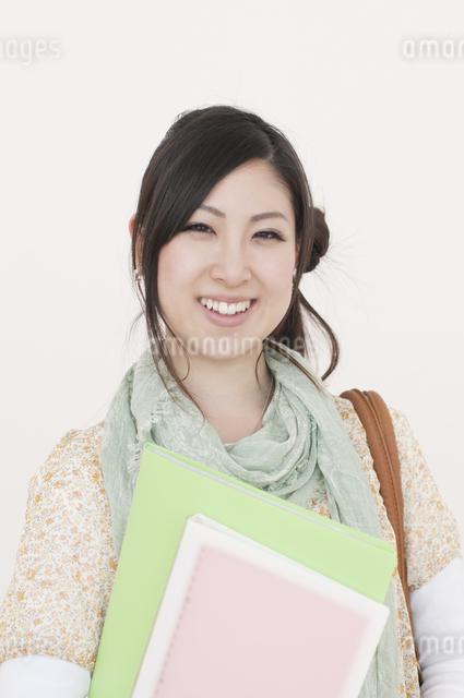 ファイルを持ち微笑む大学生の写真素材 [FYI04547069]