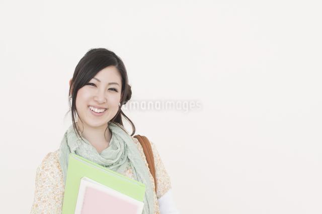 ファイルを持ち微笑む大学生の写真素材 [FYI04547075]