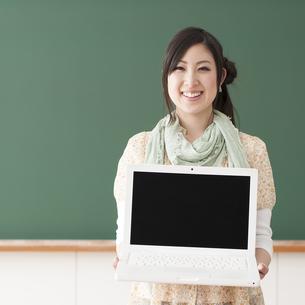 ノートパソコンを持ち微笑む大学生の写真素材 [FYI04547089]