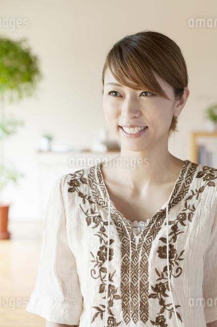 部屋で微笑む女性の写真素材 [FYI04547159]