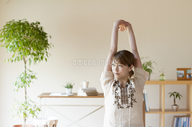 部屋でストレッチをする女性の写真素材 [FYI04547164]